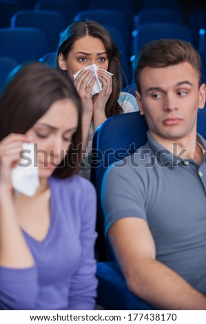 This movie is for ladies only. Bored young man sitting together with crying women while watching movie at the cinema - stock photo