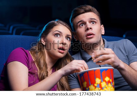 This movie is so scary! Shocked young couple eating popcorn and watching movie together while sitting at the cinema
