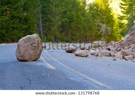 This national forest road is blocked by a land slide of rock and debris to where it is a hazard for drivers in cars. - stock photo