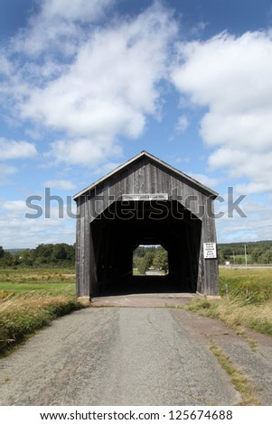 This old covered bridge is no longer in use except to foot traffic, lovingly restored and now a local landmark. Found in New Brunswick, Canada, it spans the Sawmill Creek near the Bay of Fundy. - stock photo