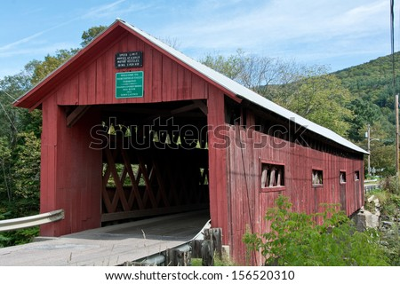 This old red wooden covered bridge crosses the Dog River in Northfield Falls, Vermont. - stock photo