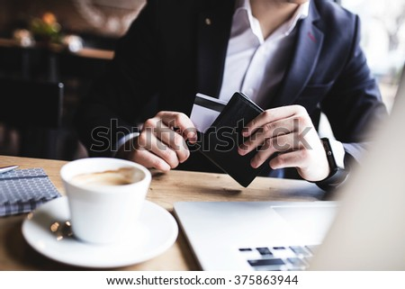 This one is on me! Man taking his credit card - stock photo