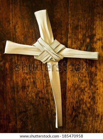 This Palm Branch was folded into a Cross shape and photographed on an antique wooden seat.  It represents the Easter Season including Palm Sunday and Good Friday. Palm Branch Cross is my creation. - stock photo