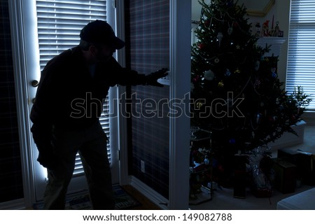This photo illustrates a burglary or thief breaking into a home at night through a back door during the Christmas Holiday Season. View from inside the residence. - stock photo