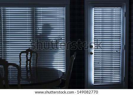 This photo illustrates a silhouette of a burglar or thief sneaking up to back door at night. View from inside the residence. - stock photo