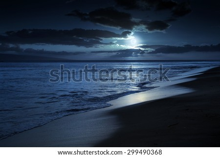 This photo illustration depicts a quiet and romantic moonlit beach in Maui Hawaii. It could represent any beach at night with calm waves and cloud filled night time sky. - stock photo