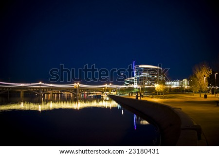 This photo is showcasing the landmark Mill Ave Bridge in Tempe Arizona. Shown here crossing the Tempe Town Lake in a night setting.