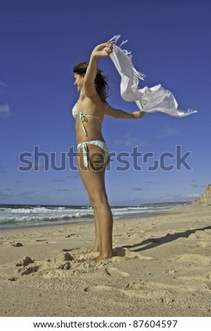 This photo shows a beautiful young lady on the beach with a white scarf waving at the wind.