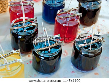This photo shows a candle maker's work bench with liquid wax in various jars and pins holding the wicks in place, many wax drips are on the tablecloth. - stock photo