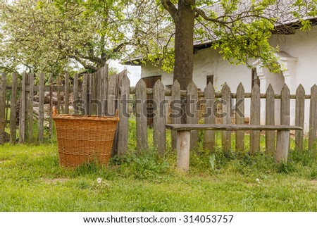 This photo shows a closeup of old wooden basket in front of fence.