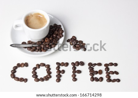 This photo shows a cup of coffee and some coffee beans creating the word coffee, illustrating the pleasure of drinking coffee !