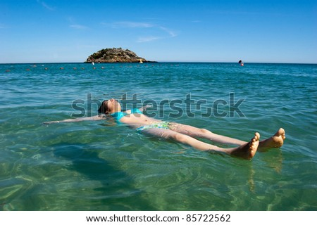 This photo shows a girl floating on the water and having fun !