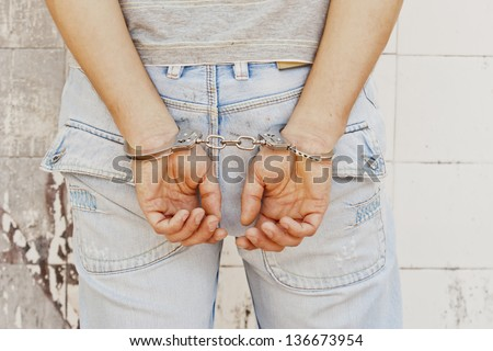 This photo shows a young men arrested with handcuffs. - stock photo