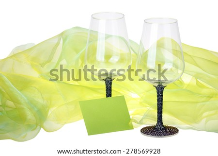 This photo shows close-up of two wine glasses surrounded by green velvet on the white background.
