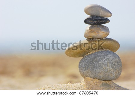 This photo shows stones that are standing on top of others on the beach.