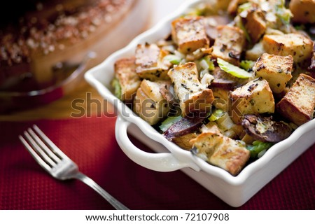 This photograph contains an image of a table setting with casserole dish of vegetables, croutons, and sausage as point of interest. - stock photo