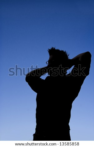 This photographic silhouette has some nice shadow detail. It is an image of a man relaxing and looking content. - stock photo