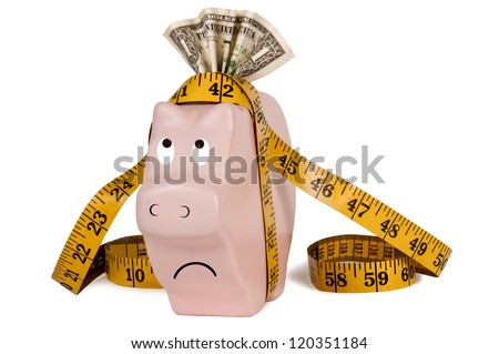 This poor piggy bank is getting slimmer and slimmer.  Many people have had to use their savings to pay bills, etc.  Has money in his slot and a measuring tape to signify tightening his belt. - stock photo