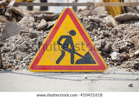 This road is under construction and closed. Yellow safety sign warns about roadworks. Be careful, danger on your way - stock photo