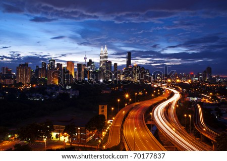 This scenario Kuala Lumpur twin towers, taken with slow shutter speed to get the light trail from the highway traffic.  lightrail view of Kuala Lumpur city - stock photo