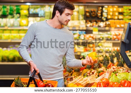 This should be fine. Handsome young men holding pepper and shopping bag while standing in a food store - stock photo