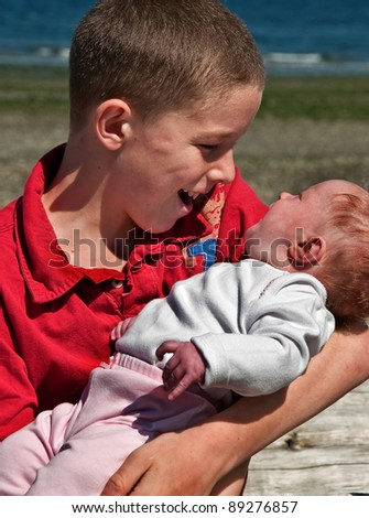 This shows a loving big brother holding and interacting with his newborn baby sister in which she is responding to his love.  Caucasian family, waist up, side view of siblings.