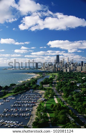 This shows Lincoln Park, Diversey Harbor, and Lake Michigan looking south toward the skyline. It has morning light in summertime. There are boats moored in the harbor next to the lake. - stock photo