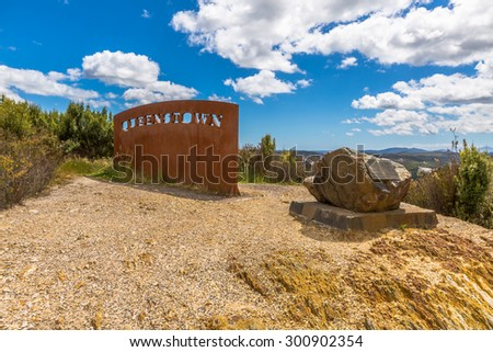 This sign decorates the Queenstown lookout, the largest town on Tasmanias west coast, is the home of the Mt Lyell Mining, Australia. - stock photo