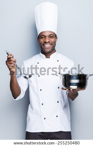 This soup is perfect! Confident young African chef in white uniform holding casserole and scoop while standing against grey background - stock photo