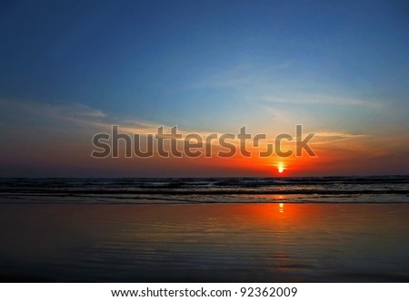This stock photo is a stunning sunset at the beach as the sun is just about to dip over the horizon.  Horizontal format this conveys of concepts of vacation, getaways, peace, tranquility, rest, quiet.