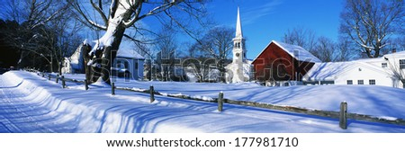 This town was settled in 1776. It is a typical image of New England in the winter. There is a white church with tall steeple, snow covered trees and wooden fence with snow. - stock photo
