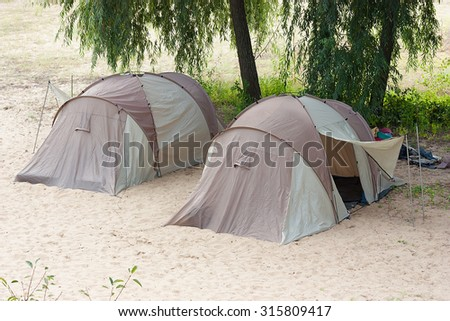 This two tent of camps of tourists in the summer on the sand.