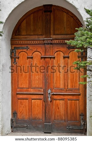 This vertical image is beautiful wooden double doors, in a rustic setting with stucco building in an archway.  Architectural element that is simply gorgeous in it's old world style. - stock photo
