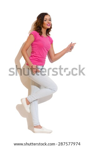 This White Space Is For Your Design. Smiling young woman standing on one leg against white wall in the sunlight and pointing. Full length studio shot on white background. - stock photo