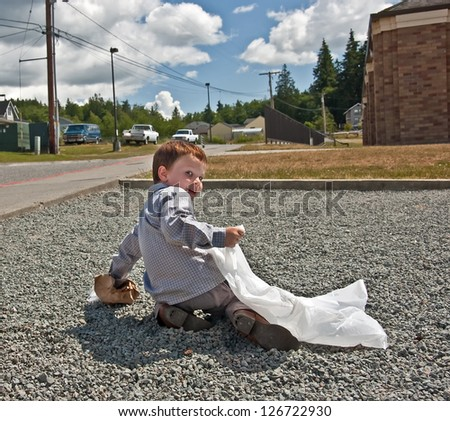 This 4 year old Caucasian boy is picking up garbage outside, a crumpled paper bag litter into a white trash bag.  He's helping the environment to stay green. - stock photo