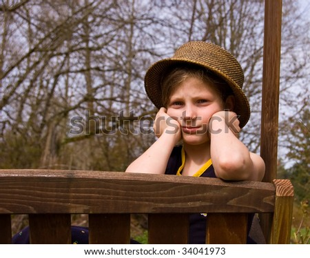 This 8 year old Caucasian girl is pouting while sitting on an outdoor swing wearing a natural hat. - stock photo