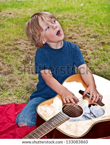 This young boy is an aspiring musician as he is singing a song, while strumming on a guitar that's laying nearby him.  He is outdoors enjoying this childhood fun. - stock photo