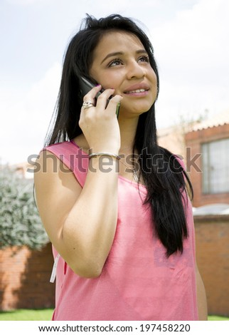 This young lady is talking by the phone and smile  - stock photo