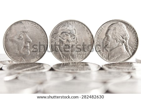Thomas Jefferson faces on three five cents coins standing on the edge white background and coins on the foreground - stock photo