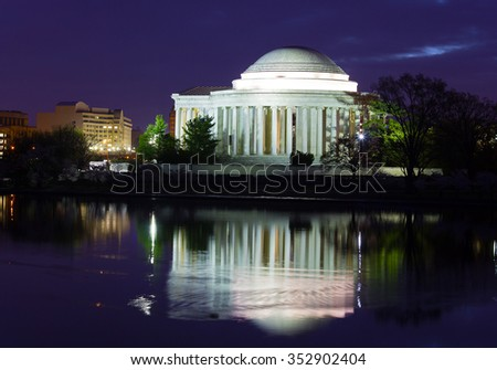 Thomas Jefferson Memorial before sunrise during cherry blossom festival in Washington DC, USA. Colorful reflection of the memorial in waters of Tidal Basin at night.