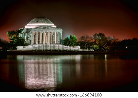 Thomas Jefferson Memorial famous American landmark with light reflections on the water of the Tidal Basin in West Potomac Park at night in the capital of the United States of Washington DC  - stock photo