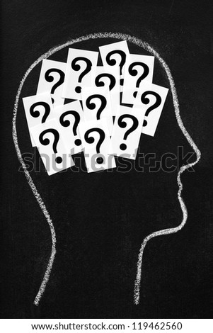 Thought process, decisions or confusion. Question marks inside chalk head on blackboard - stock photo