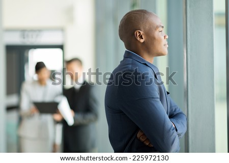thoughtful african american businessman inside an office building looking outside the window - stock photo