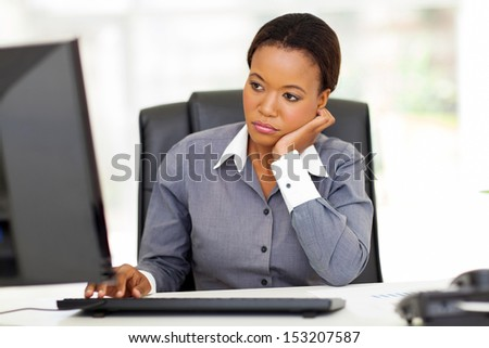 thoughtful african american businesswoman looking at computer screen in office