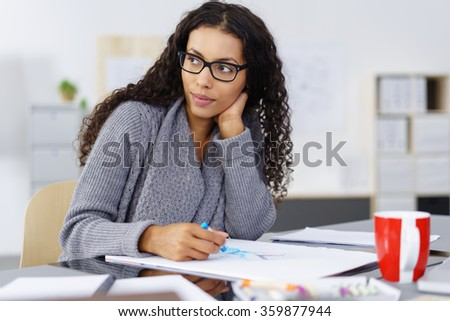 Thoughtful African American design artist sitting at her desk in the office sketching on a pad with colored crayons looking off to the side - stock photo