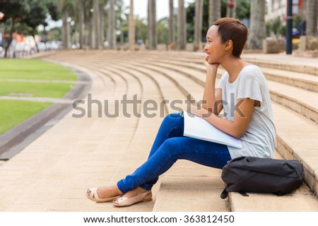 thoughtful african american university student relaxing outdoors - stock photo