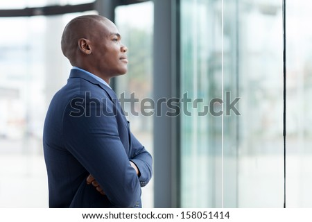 thoughtful african businessman with arms crossed in office - stock photo