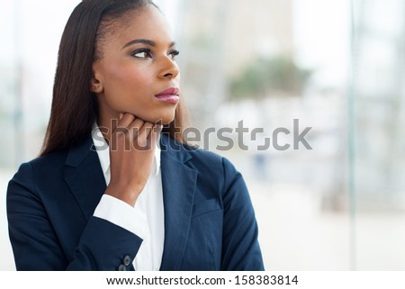 thoughtful african businesswoman looking through window  - stock photo