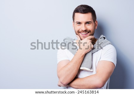 Thoughtful and handsome.  Portrait of young man holding hand on chin and looking at camera while standing against grey background.  - stock photo