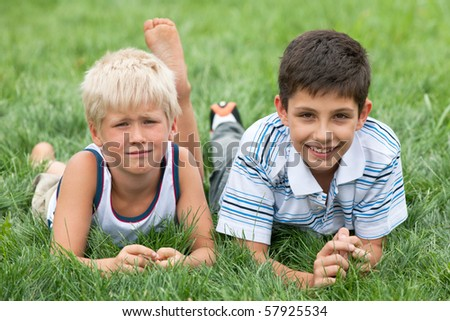 Thoughtful and smiling boys are lying on the green grass